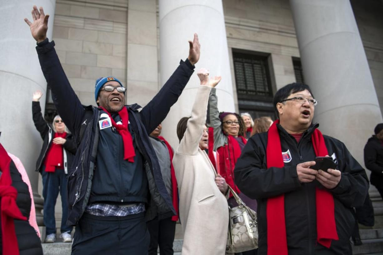 """Amon Rutherford of Vancouver, left, and Gary Akizuki, right, cheer as the 17th Legislative District is called during a rally at Housing and Homelessness Advocacy Day on the Capitol steps in Olympia. Akizuki has been coming to the advocacy day since 2003 when a smaller crowd met with legislators. """"The things we do up here, lobbying, makes a difference,"""" he said."""