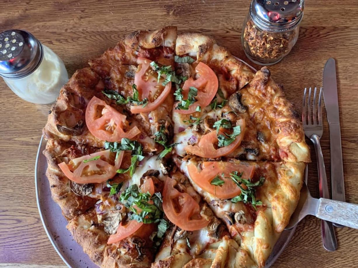 A custom pizza with red onions, mushrooms, fresh tomatoes, and fresh basil at Prairie Bar & Grill. (Rick Browne)