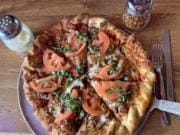 A custom pizza with red onions, mushrooms, fresh tomatoes, and fresh basil at Prairie Bar & Grill.