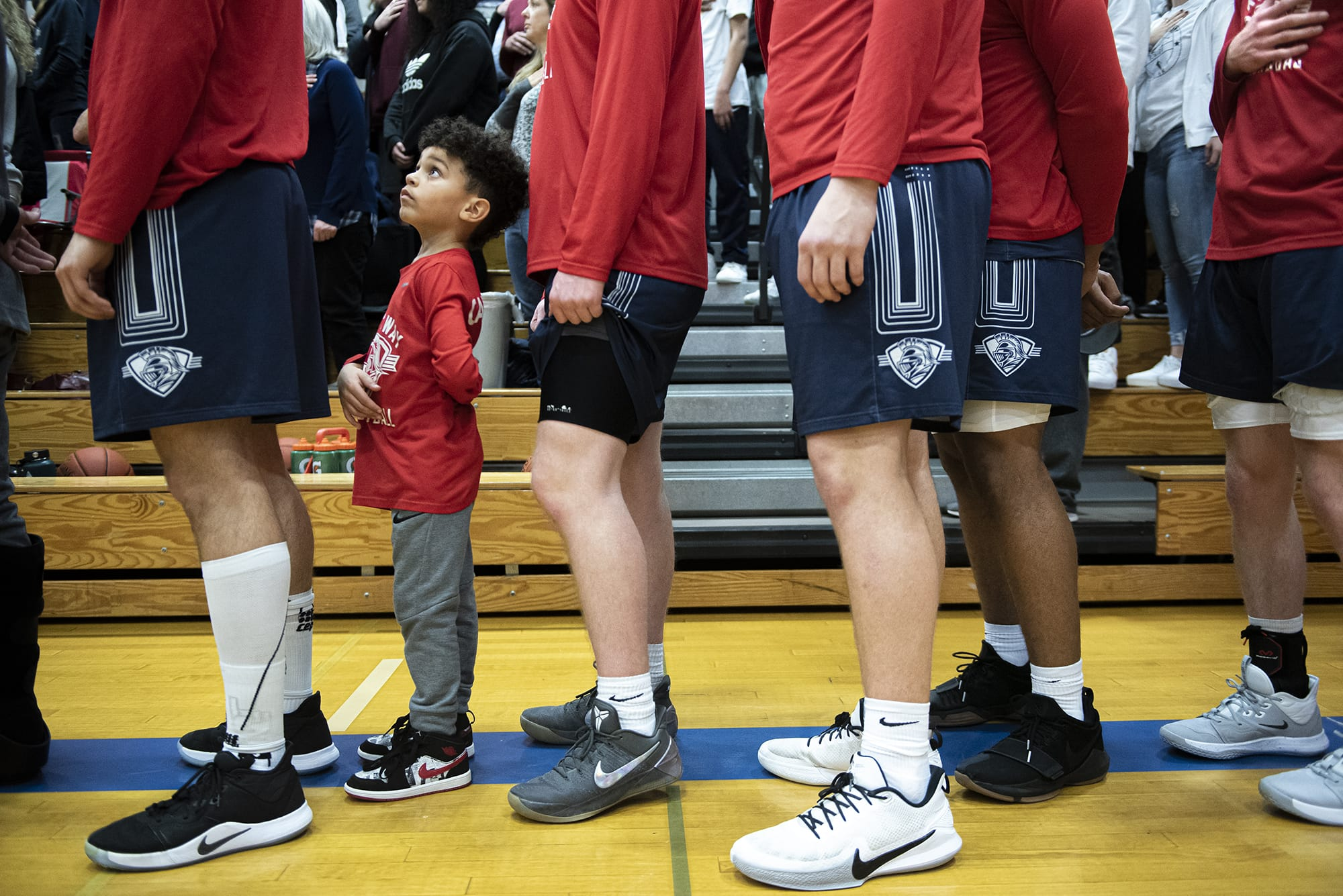 Cayson Bay, son of King's Way assistant coach Kal Bay, stands with the team during the National Anthem prior to their game against La Center at La Center High School on Thursday night, Feb. 6, 2020. (Nathan Howard/The Columbian)