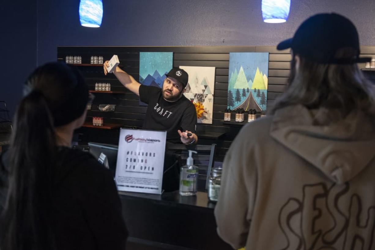 Mike Roth, manager at Fatboy Vapors on Chkalov Drive, tells customers on Friday that he will have flavored vape juice in stock today. (Nathan Howard/The Columbian) (Photos by Nathan Howard/The Columbian)