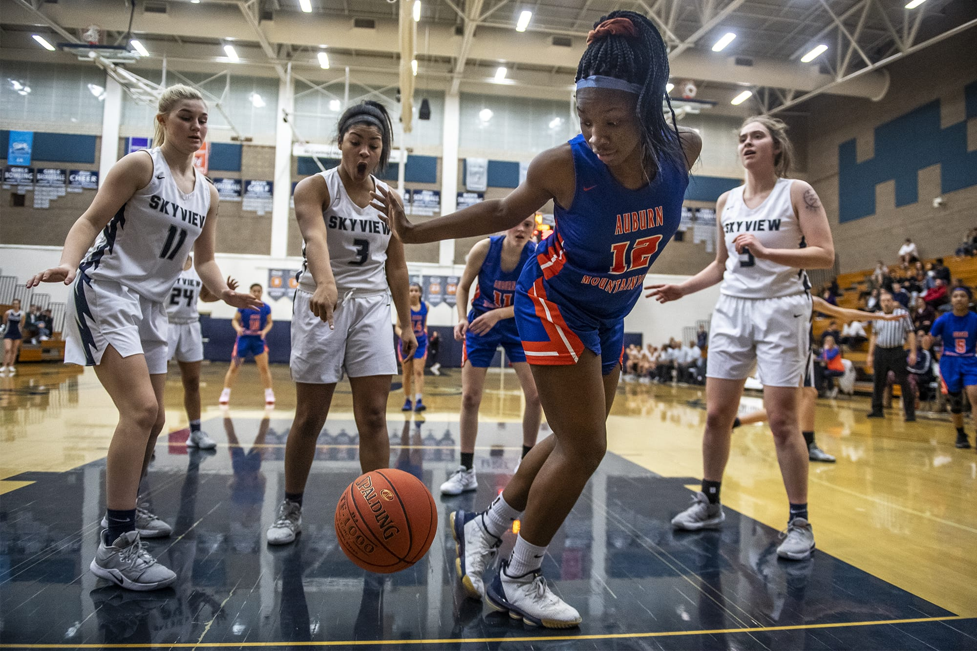 Skyview's Mikelle Anthony, center left, reacts to Auburn's Azaria Johnson's efforts to keep the ball in bounds during a game at Skyview High School on Thursday night, Feb. 13, 2020. (Nathan Howard/The Columbian)