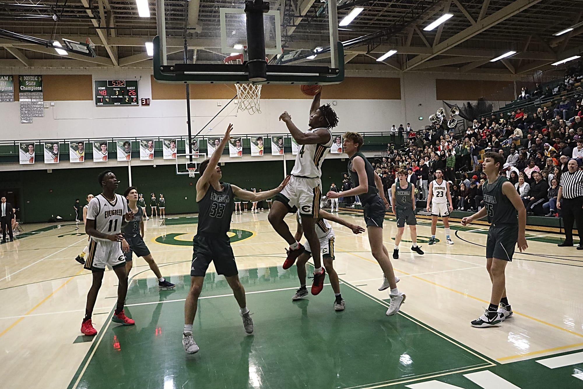 Evergreen's Cole McVay, center goes up for a shot against Peninsula in a winner-to-state game in the 3A boys basketball bi-district tournament on Saturday night, Feb. 15, 2020.