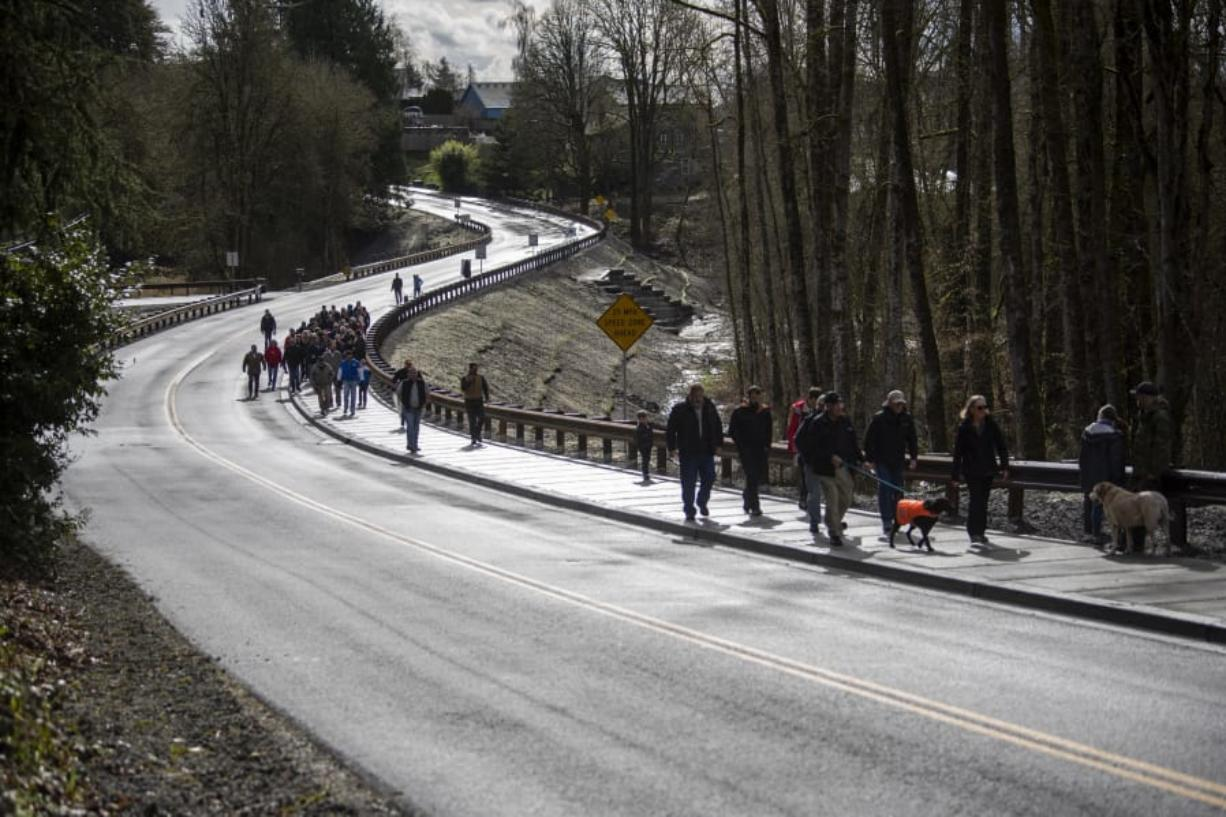 Walkers make their way down Main Avenue before the ribbon cutting ceremony Friday to celebrate the completion of the John Hudson Trail over the remodeled Gee Creek Crossing at the Ridgefield National Wildlife Refuge. (Alisha Jucevic/The Columbian)