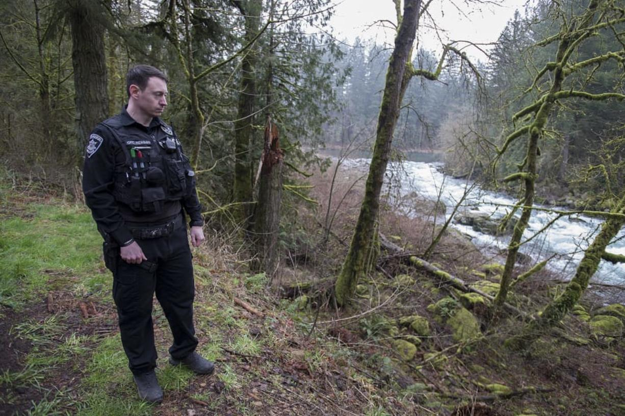 Washougal police Officer Francis Reagan pauses Thursday near the spot along the Washougal River where he rescued a woman from the water. (Amanda Cowan/The Columbian)