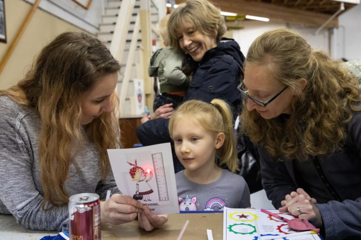 Engineering volunteer Caitlyn Bodda, from left, Agnes Himmelber, 5, Johnny Himmelber, 1, Marian Waggener and Meagan Himmelber, all of Ridgefield, test a circuit made from paper, copper tape and a small battery during Saturday's Rosie Revere Engineer Day at Pearson Field Education Center.