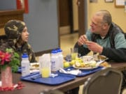 Donnie Rousey, 14, left, eats dinner with Mark Traxler, who is homeless and lives in Washougal, during Refuel Washougal's free weekly meal at the Washougal Community Center.