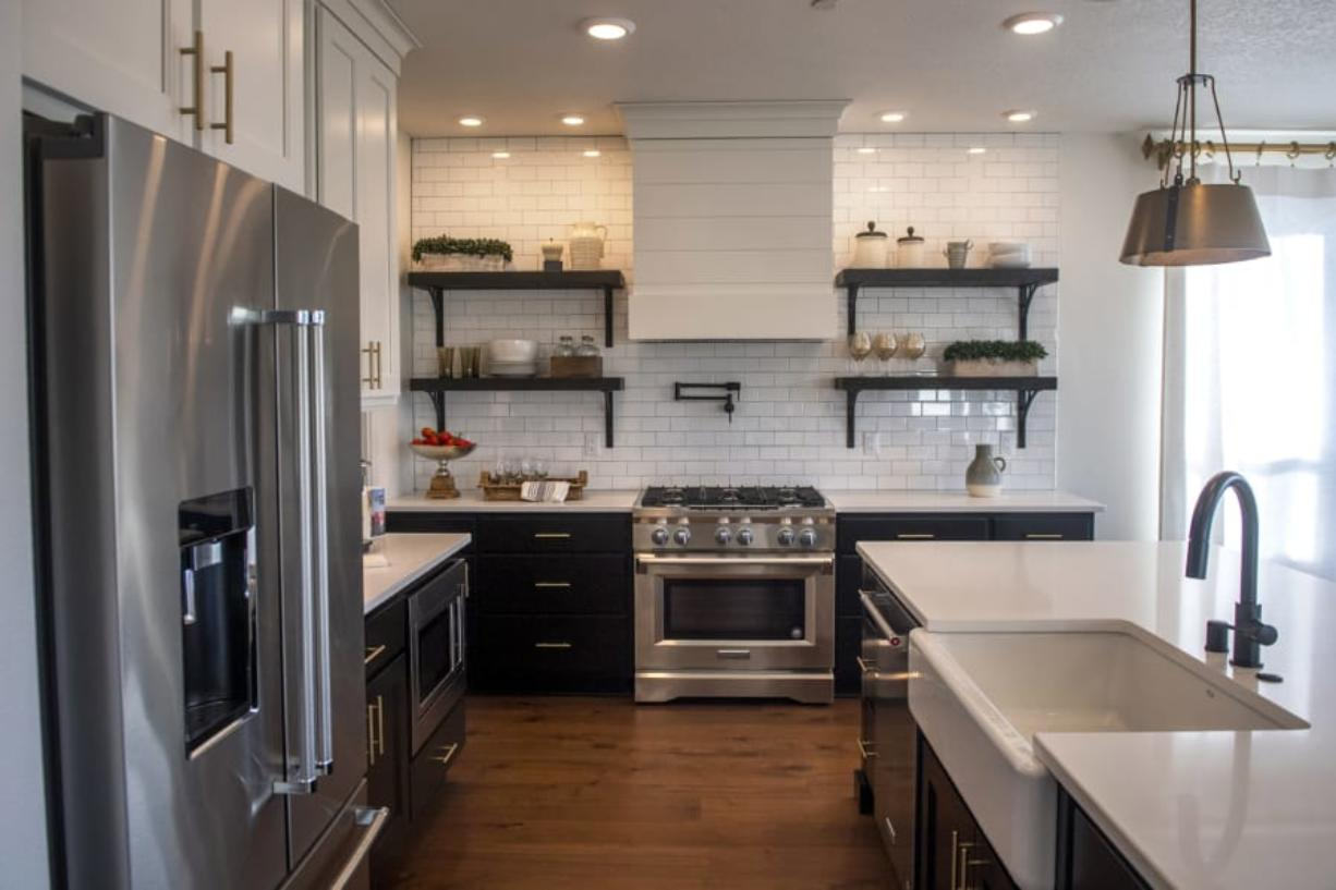 The kitchen in a New Tradition Homes model house at the Velvet Acres development in Vancouver highlights a recent design trend: A move away from all-white kitchens in favor of dark wood or painted cabinets.