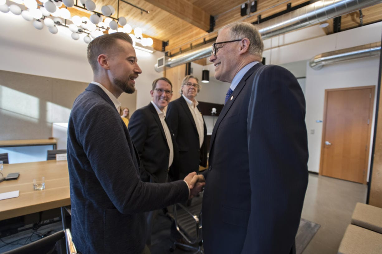 Sean McClain, founder and CEO of AbSci, left, greets Gov. Jay Inslee at the AbSci offices in downtown Vancouver on Thursday. Inslee helped the company finance a move to Vancouver in 2016, and AbSci has seen massive growth since then. Also pictured are AbSci's Johan Kers, second from left, and Fred Larimore.