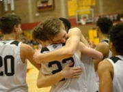 Union senior Tanner Toolson hugs teammate Kaden Horn after the 4A bi-district boys basketball championship game against Battle Ground at Prairie High School on Saturday, February 22, 2020. Union beat Battle Ground 82-57.