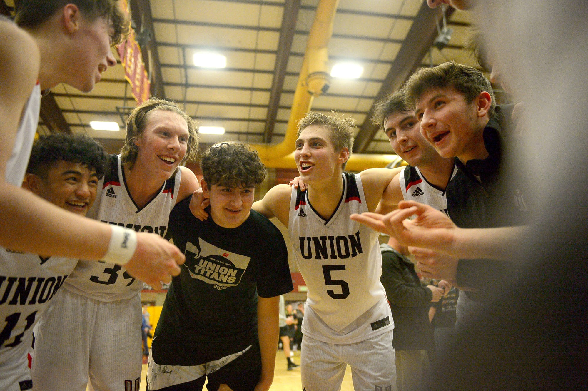The Union boys basketball team celebrates after the 4A bi-district championship game against Battle Ground at Prairie High School on Saturday, February 22, 2020. Union beat Battle Ground 82-57. (Samuel Wilson for the Columbian)