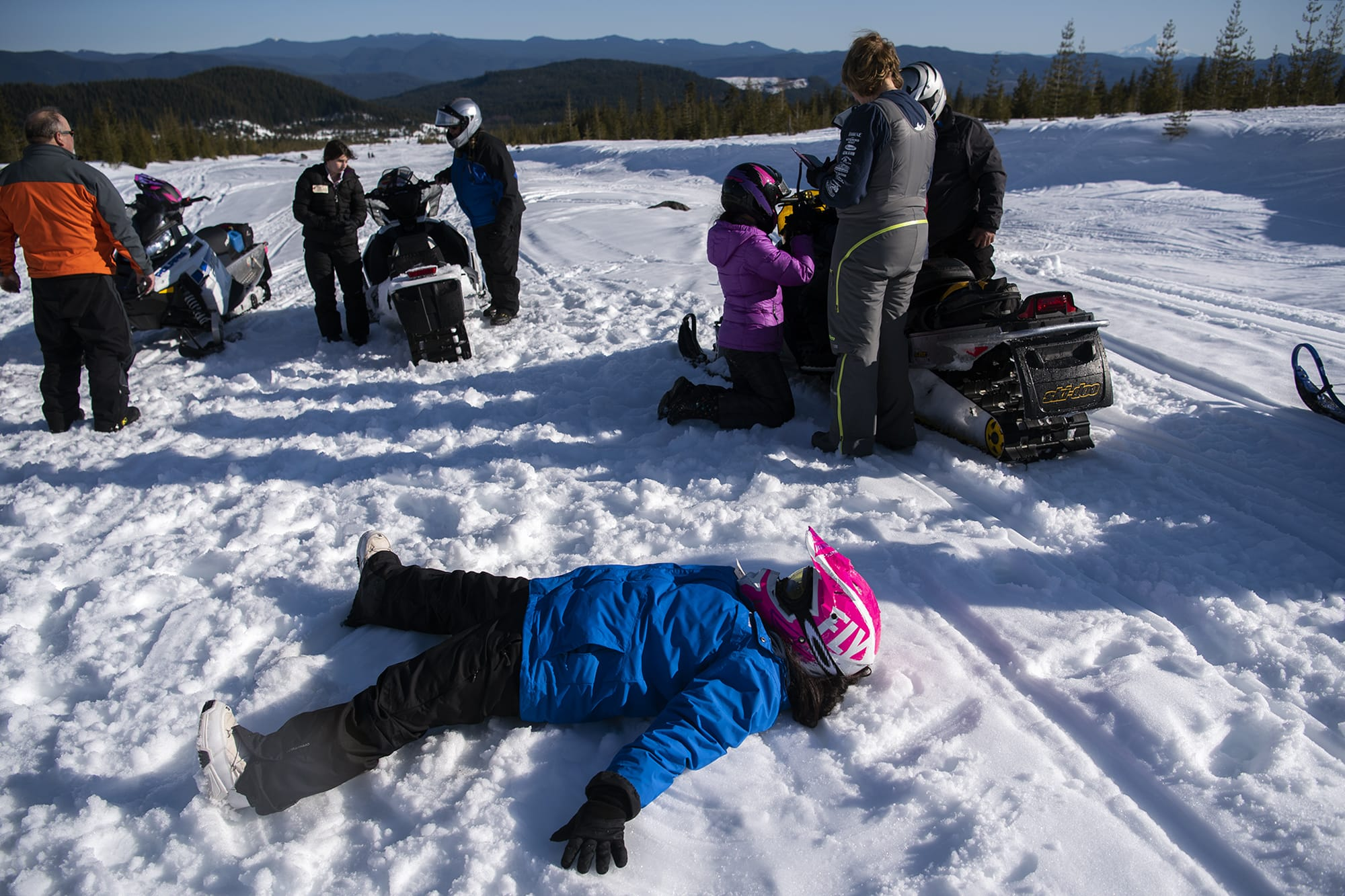 Washington State School for the Blind eighth-grader Angie Rodriguez makes a snow angel as the group takes a break from snowmobiling at Marble Mountain Sno-Park near Mount Saint Helens on Feb. 27, 2020. (Alisha Jucevic/The Columbian)