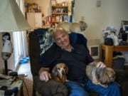 Bill Hoover sits with his dogs Daisey, left, Gotcha, right, and his friend's dog Pozey, back, at his apartment in Vancouver. Hoover's dogs love to sit on his lap while he's in his recliner.