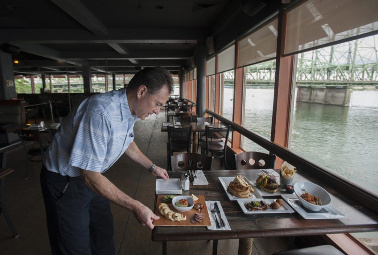 Owner Mark Matthias serves up food at WareHouse '23. The restaurant is scheduled to close at the end of this year after four-and-a-half years in operation. (Amanda Cowan/The Columbian files)