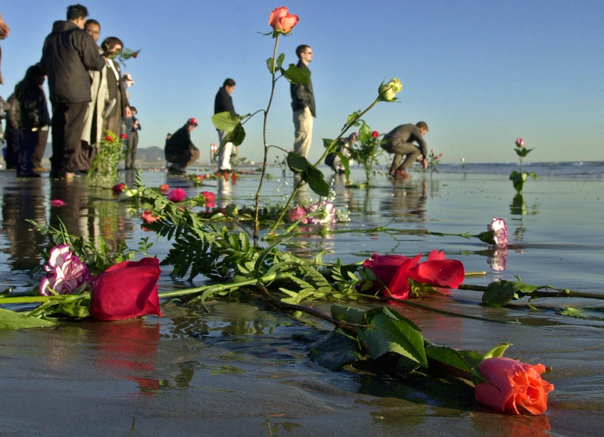 Waves lap over roses left in the surf by family members of victims after ceremonies to dedicate a monument to remember the victims of Alaska Airlines Flight 261, which plunged into the sea about eight miles offshore two years ago, at Port Hueneme Beach Park Thursday, Jan. 31, 2002, in Port Hueneme, Calif.  The crash took 88 lives when the jetliner crashed at 4:21 p.m. on Jan. 31, 2000.  (AP Photo/Reed Saxon)