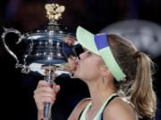 Sofia Kenin of the U.S. kisses the Daphne Akhurst Memorial Cup after defeating Spain's Garbine Muguruza in the women's singles final at the Australian Open tennis championship in Melbourne, Australia, Saturday, Feb. 1, 2020.