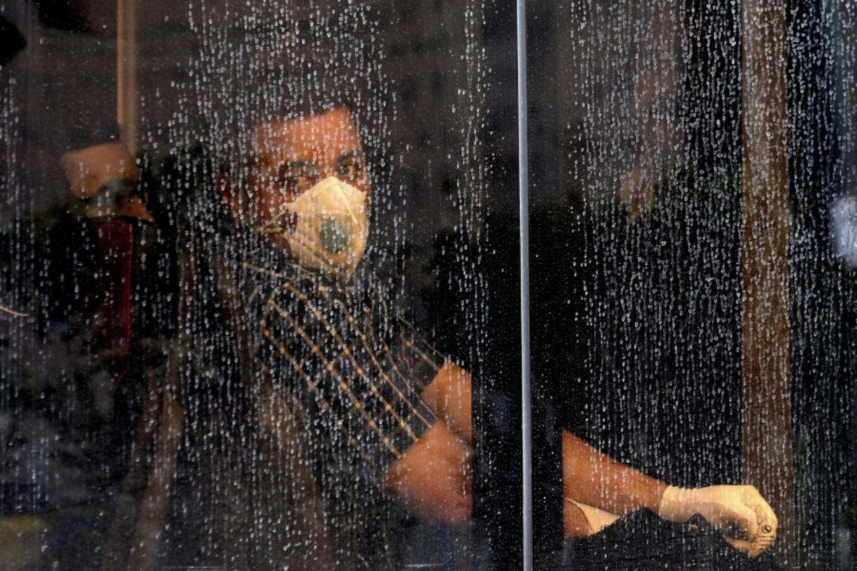 A commuter looks through a water-stained window wearing a mask and gloves to help guard against the Coronavirus, on a public bus in downtown Tehran, Iran, Sunday, Feb. 23, 2020. Iran's health ministry raised Sunday the death toll from the new virus to 8 people in the country, amid concerns that clusters there, as well as in Italy and South Korea, could signal a serious new stage in its global spread.