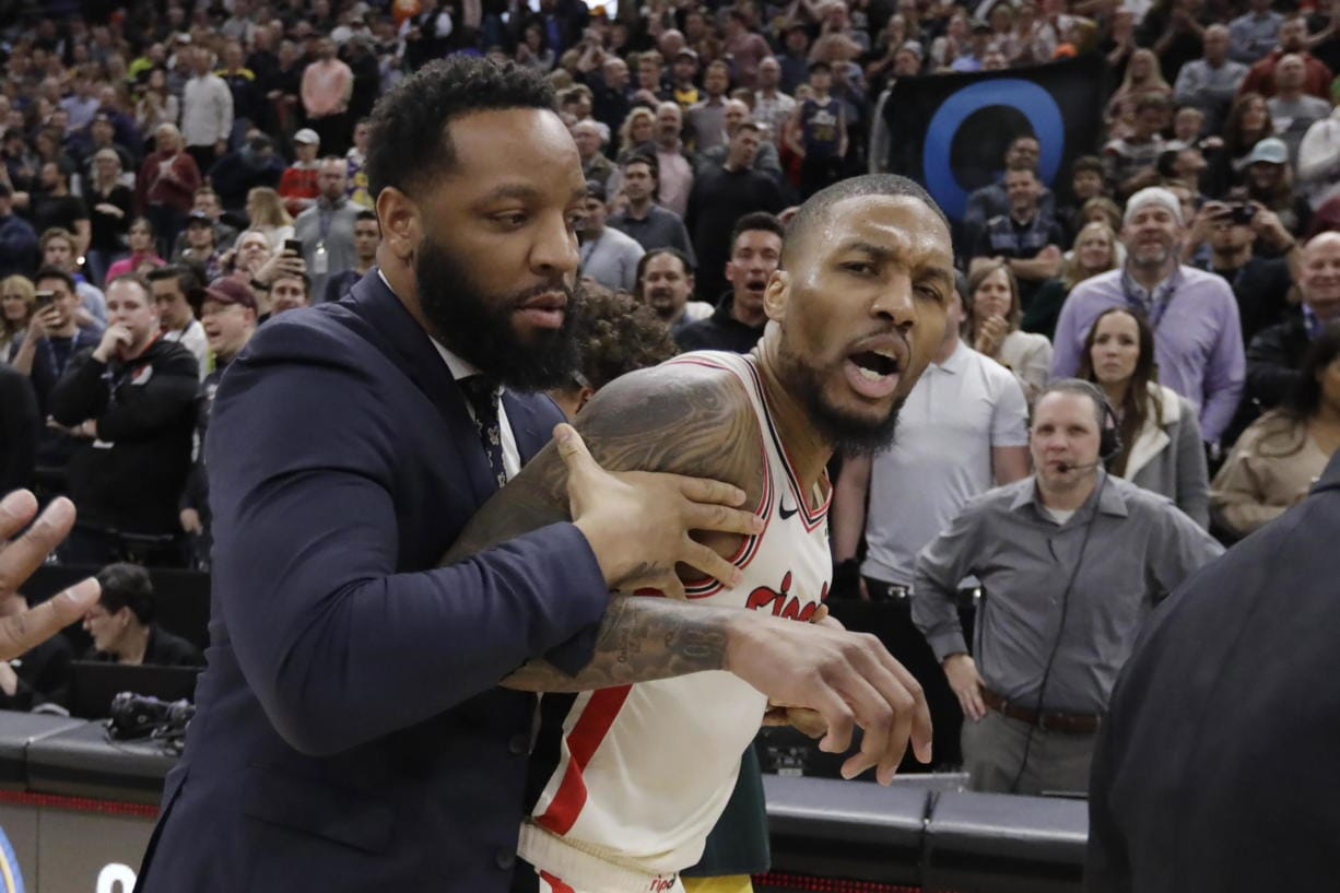 Portland Trail Blazers guard Damian Lillard (0) is held back following the team's NBA basketball game against the Utah Jazz of Friday Feb. 7, 2020, in Salt Lake City. The Jazz won 117-114. (AP Photo/Rick Bowmer)