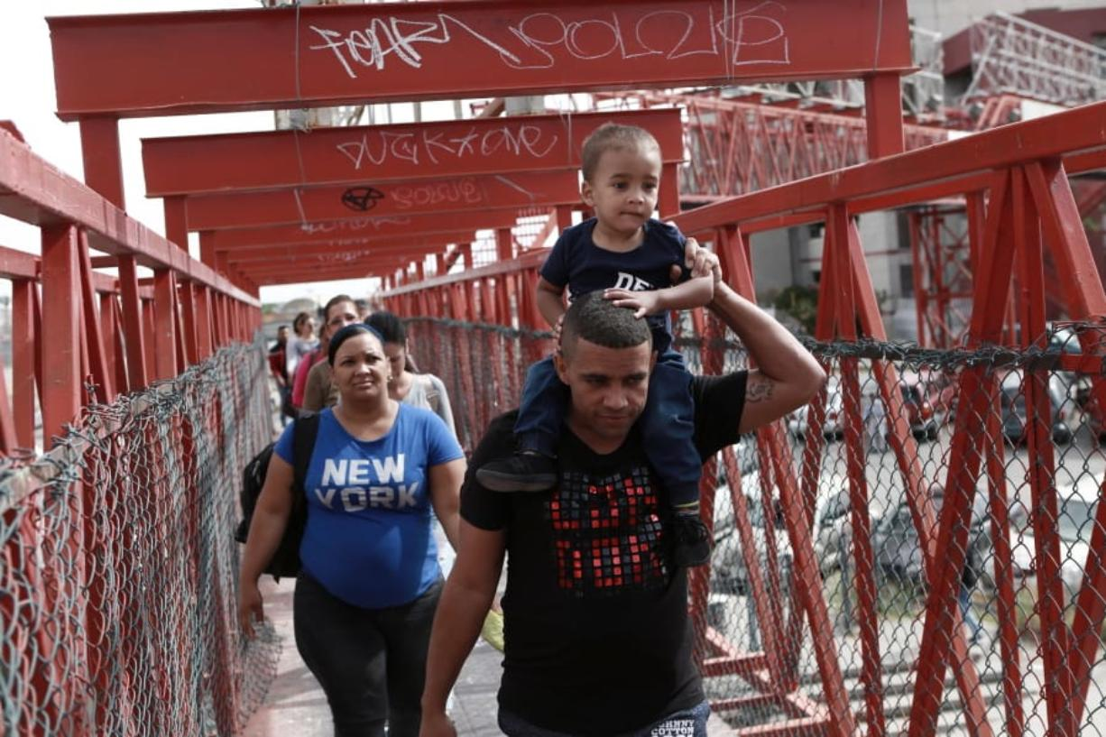 FILE - In this April 29, 2019, file photo, Cuban migrants are escorted in Ciudad Juarez, Mexico, by Mexican immigration officials as they cross the Paso del Norte International bridge to be processed as asylum seekers on the U.S. side of the border. (AP Photo/Christian Torres, File)