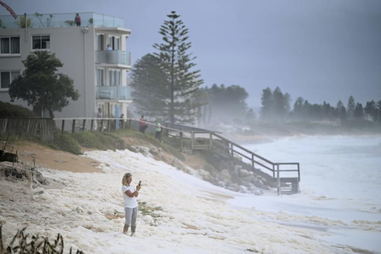 A resident inspects sea foam brought by waves approaching on beach front houses after heavy rain and storms at Collaroy in Sydney's Northern Beaches, Monday, February 10, 2020. Drought, wildfires and now flooding have given Australia's weather an almost Biblical feel this year. The good news is that a deluge in eastern parts of the country over recent days has helped dampen deadly fires and ease a crippling drought.