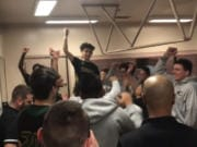 Izaac Romero (standing, facing camera) and the Evergreen Plainsmen celebrate their 75-70 overtime victory over Mount Tahoma on Thursday to advance to Saturday's bi-district title game.