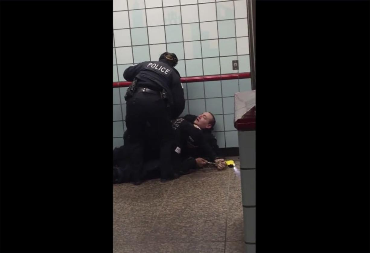 This image from cellphone video shows Chicago police officers trying to apprehend a suspect in a downtown train station.