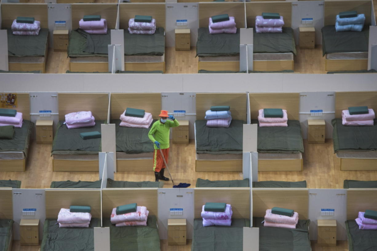In this photo released by Xinhua News Agency, a worker cleans the floor of a temporary hospital with 1,100 beds converted from the Wuhan Sports Center in Wuhan in central China's Hubei Province, Wednesday, Feb. 12, 2020. Without enough facilities to handle the number of cases of viral infection, Wuhan has been building prefabricated hospitals and converting a gym and other large spaces to house patients and try to isolate them from others.