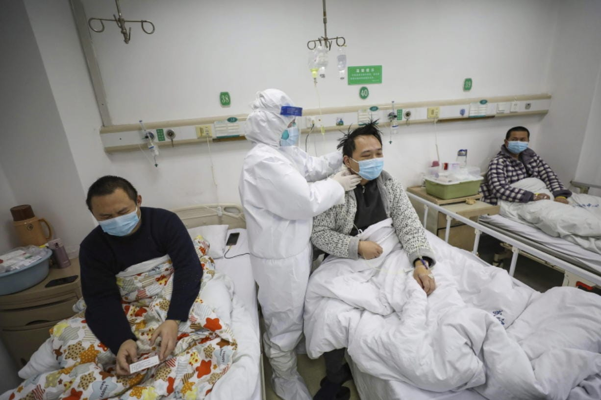 A doctor checks the conditions of a patient in Jinyintan Hospital, designated for critical COVID-19 patients, in Wuhan in central China's Hubei province Thursday, Feb. 13, 2020. China on Thursday reported 254 new deaths and a spike in virus cases of 15,152.