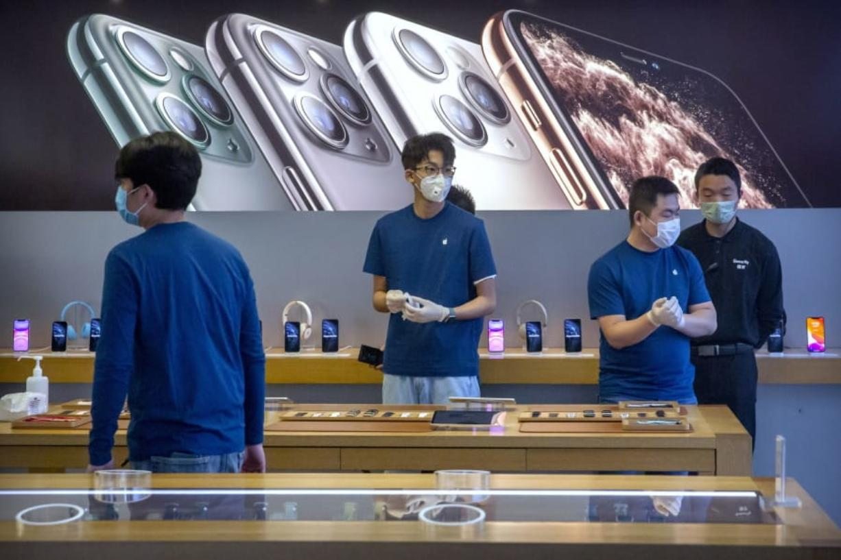 FILE - In a Feb. 14, 2020 file photo, employees wear face masks as they stand in a reopened Apple Store in Beijing. Apple Inc. is warning investors that it won't meet its second-quarter financial guidance because the viral outbreak in China has cut production of iPhones. The Cupertino, California-based company said Monday, Feb. 17, 2020 that all of its iPhone manufacturing facilities are outside Hubei province, and all have been reopened, but production is ramping up slowly.
