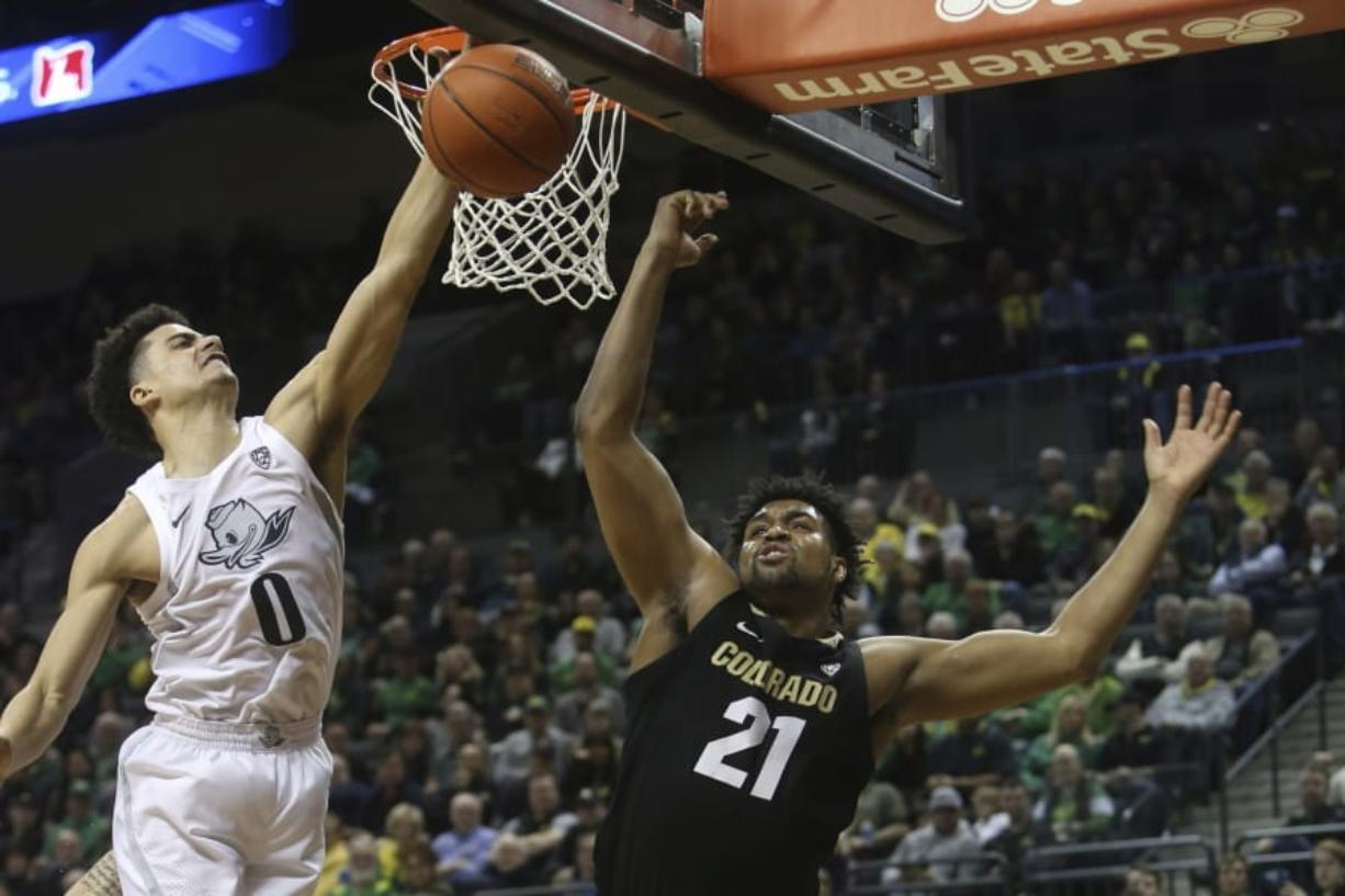 Oregon's Will Richardson, left, and Colorado's Evan Battey, center, go up for a rebound during the second half of an NCAA college basketball game in Eugene, Ore., Thursday, Feb. 13, 2020.