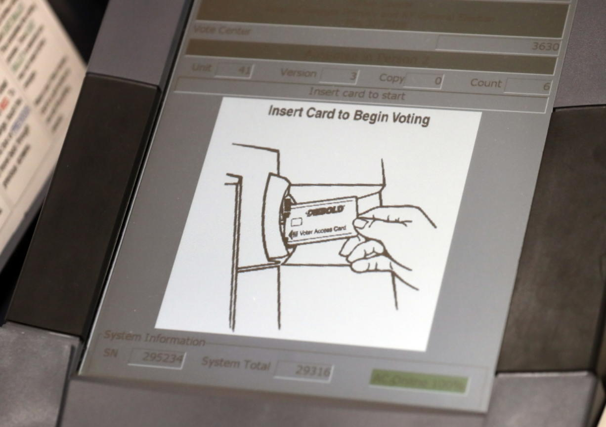 FILE - This May 9, 2018, file photo, shows a touch screen of a voting machine during early voting in Sandy Springs, Ga. In the rush to find reliable new voting machines, many state and local officials are turning to pricey models that some computer security experts see as risky. Called ballot-marking devices, the machines have touchscreens for registering voter choice. (AP Photo/John Bazemore, File)