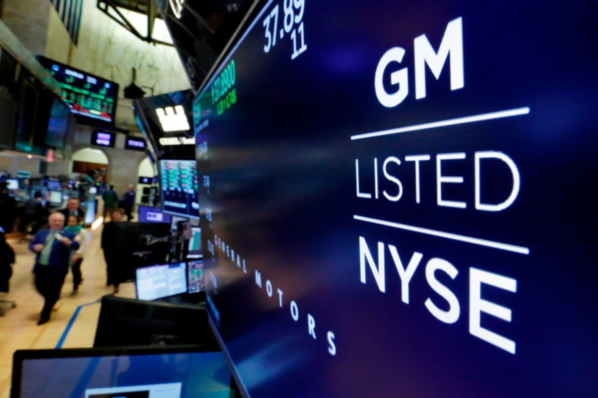 FILE - In this April 23, 2018, file photo, the logo for General Motors appears above a trading post on the floor of the New York Stock Exchange.  Despite a 40-day strike by factory workers and slumping sales in the U.S. and China, General Motors still made money in 2019. The company posted a $6.58 billion profit for the year, but that was down almost 17% from 2018.