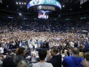 BYU students and fans celebrate on the court following BYU's 91-78 victory over Gonzaga in an NCAA college basketball game Saturday, Feb. 22, 2020, in Provo, Utah.