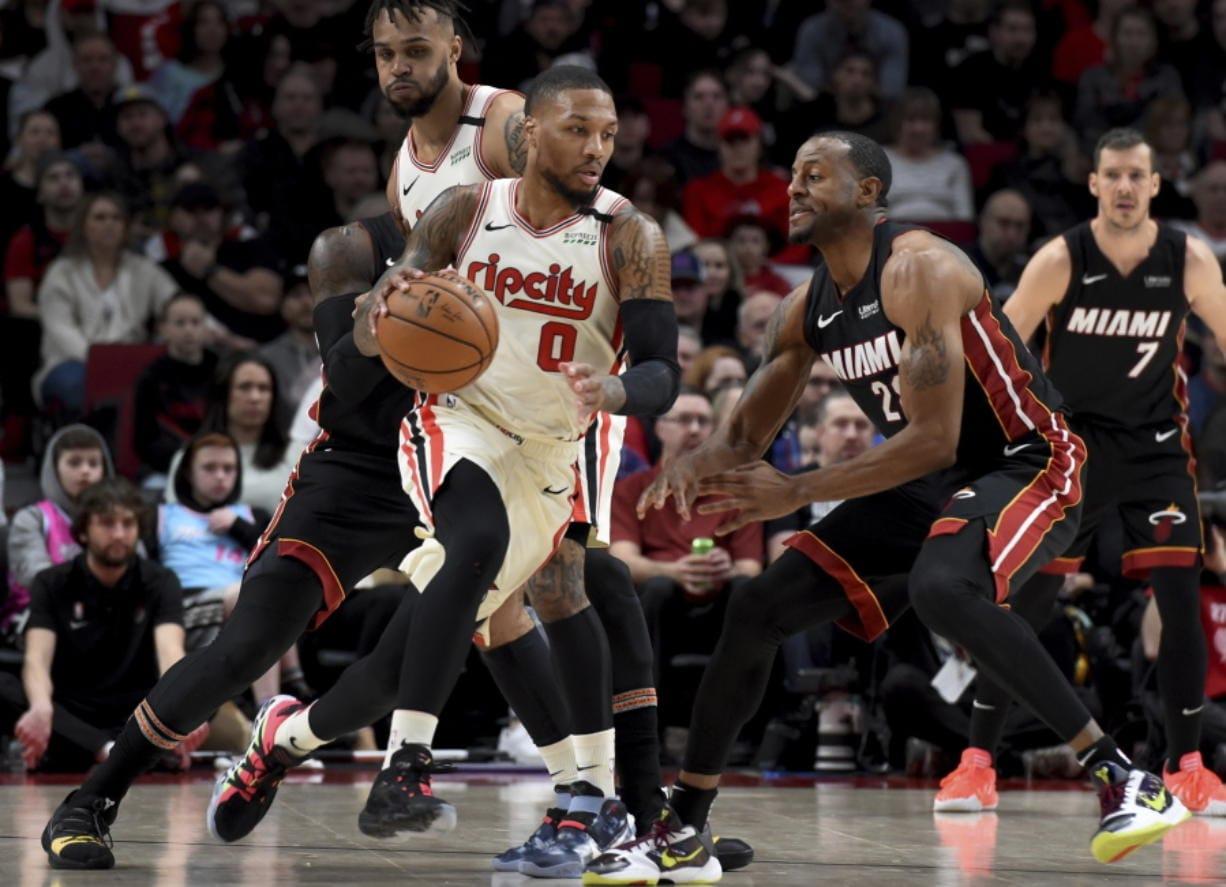 Portland Trail Blazers guard Damian Lillard, left, dribbles the ball around, Miami Heat guard Andre Iguodala, right, during the first half of an NBA basketball game in Portland, Ore., Sunday , Feb. 9, 2020.