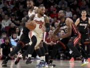 Portland Trail Blazers guard Damian Lillard, left, dribbles the ball around, Miami Heat guard Andre Iguodala, right, during the first half of an NBA basketball game in Portland, Ore., Sunday , Feb. 9, 2020.