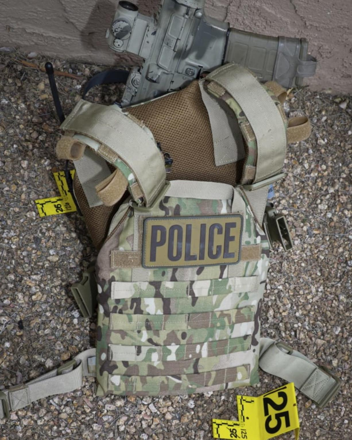 This April 11, 2019 photo provided by the Phoenix Police Department shows a Home Security Investigations agent's camouflage M4 rifle and armored vest at the scene of an agent-involved shooting in Phoenix, Ariz. The shooting although extreme, was not an isolated incident. Since 2011, there have been at least 13 shootings involving HSI agents 'Ai most of them in 2018-19, according to an investigation by the Howard Center for Investigative Journalism.