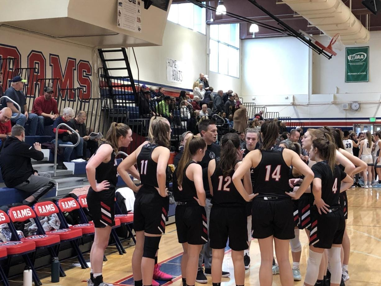 Union girls basketball coach Gary Mills huddles with his team during a 50-36 win over Rogers in a bi-district playoff game Saturday in Tacoma. (Micah Rice/The Columbian)