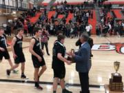 The Woodland boys basketball team receives the 2A district tournament runner-up trophy from tournament director Rob Blackman after a 63-28 loss to Tumwater in the championship game Friday at Battle Ground High School.