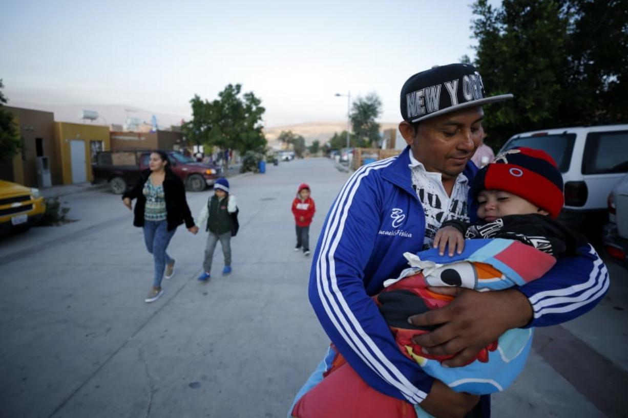 Juan Carlos Perla carries his youngest son, Joshua Mateo Perla, as the family leaves their home July 10, 2019, in Tijuana, Mexico, for an asylum hearing in San Diego.