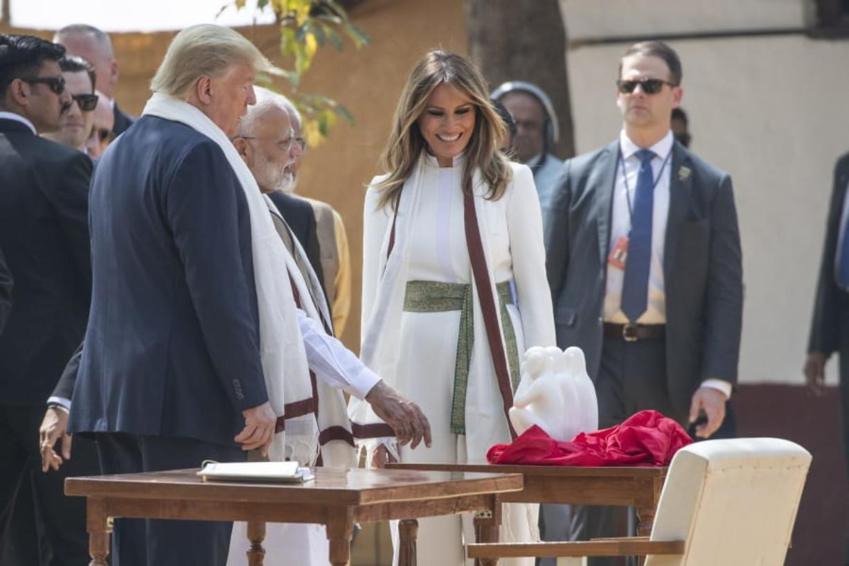 U.S. President Donald Trump, with first lady Melania Trump, look at a gift from Indian Prime Minister Narendra Modi, as they tour Gandhi Ashram, Mondayin Ahmedabad, India. (Alex Brandon/Associated Press)