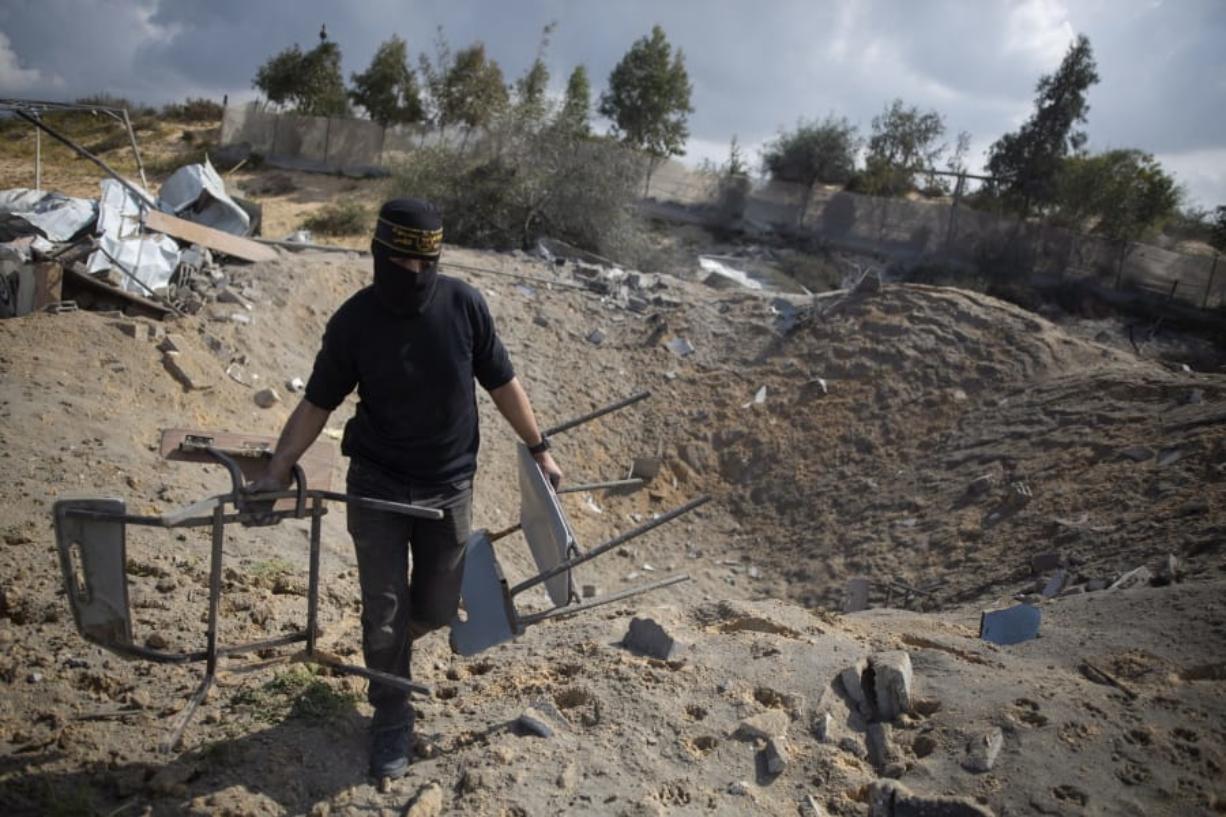 A masked Palestinian militant checks the damage following overnight Israeli airstrikes on an Islamic Jihad military base in the town of Khan Younis, Southern Gaza Strip, Monday, Feb. 24, 2020. (AP Photo/Khalil Hamra) (Adel Hana/Associated Press)