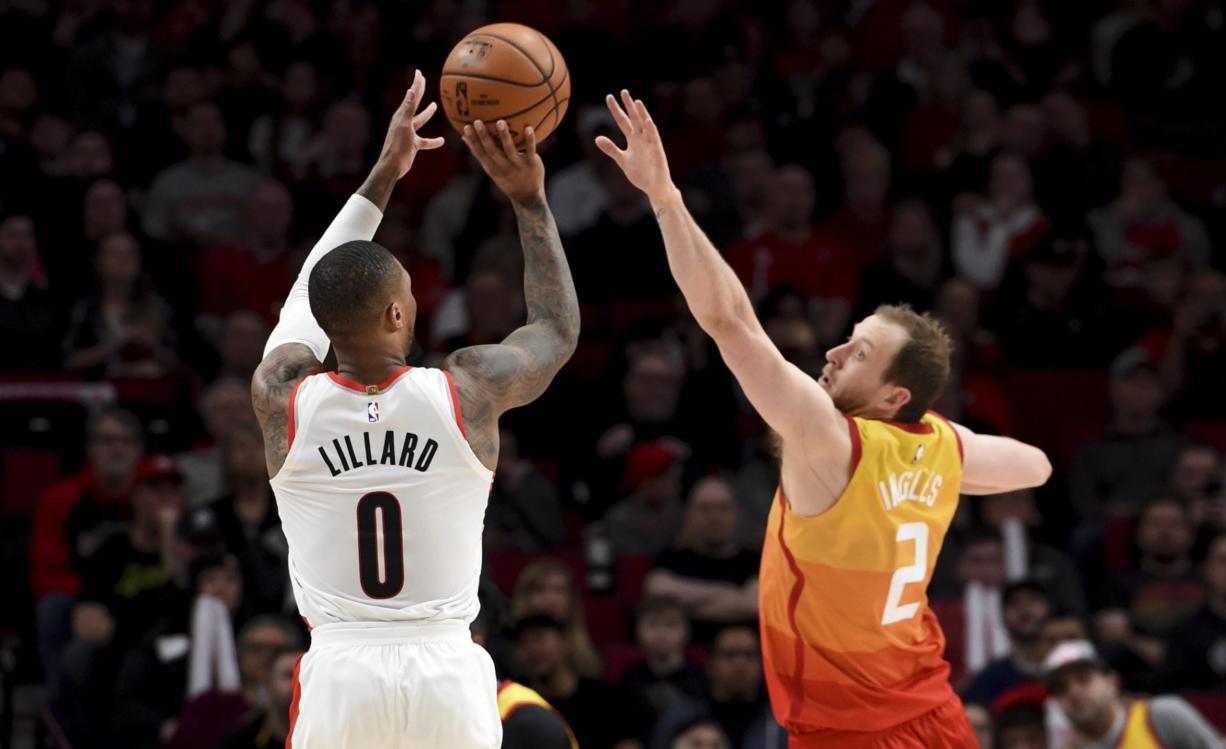 Portland Trail Blazers guard Damian Lillard, left, hits a shot over Utah Jazz guard Joe Ingles, right, during the second half of an NBA basketball game in Portland, Ore., Saturday, Feb. 1, 2020. The Blazers won 124-107. (AP Photo/Steve Dykes)