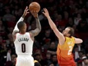 Portland Trail Blazers guard Damian Lillard, left, hits a shot over Utah Jazz guard Joe Ingles, right, during the second half of an NBA basketball game in Portland, Ore., Saturday, Feb. 1, 2020. The Blazers won 124-107.