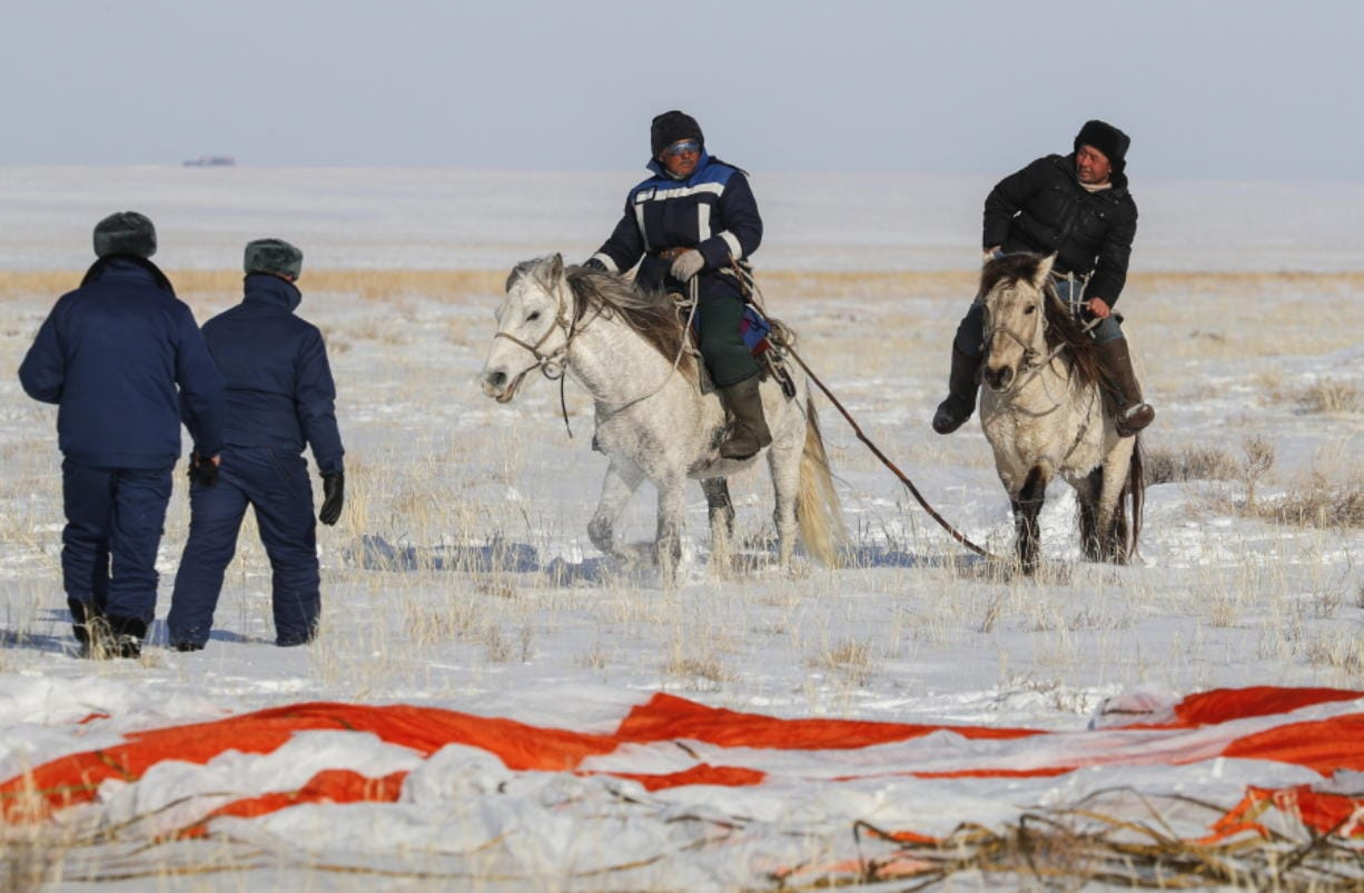 Kazakh shepherds ride near a parachute close to the place where Russian Soyuz MS-13 space capsule landed about 150 km (90 miles) south-east of the Kazakh town of Zhezkazgan, Kazakhstan, Thursday, Feb. 6, 2020. A Soyuz space capsule with U.S. astronaut Christina Koch, Italian astronaut Luca Parmitano and Russian cosmonaut Alexander Skvortsov, returning from a mission to the International Space Station landed safely on Thursday on the steppes of Kazakhstan. (Sergei Ilnitsky/Pool Photo via AP)