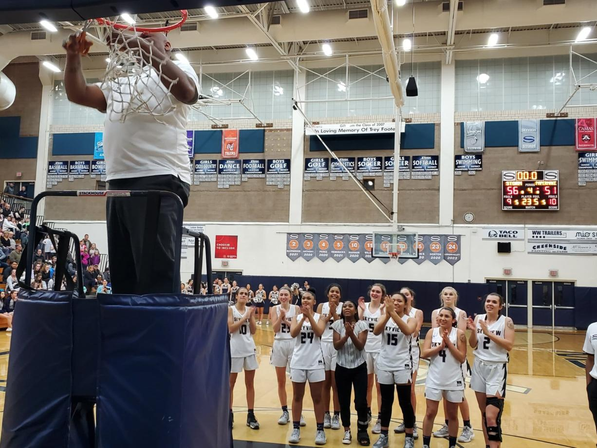 Skyview coach Brett Johnson cuts the net as the Skyview players applaud after the Storm beat Camas 56-51 to clinch the 4A Greater St.