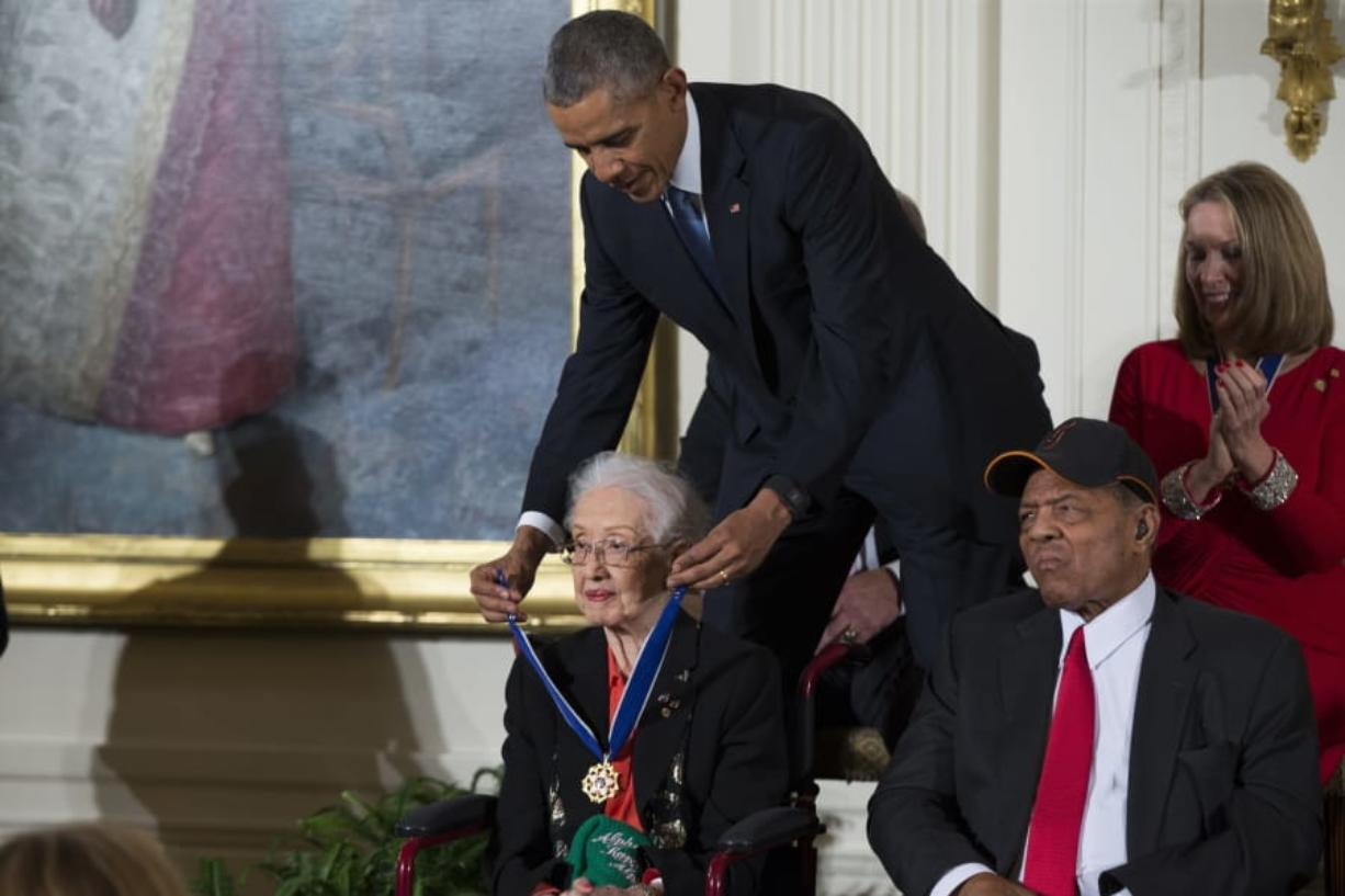 "FILE - In this Nov. 24, 2015 photo, Willie Mays, right, looks on as President Barack Obama presents the Presidential Medal of Freedom to NASA mathematician Katherine Johnson during a ceremony in the East Room of the White House, in Washington. Johnson, a mathematician on early space missions who was portrayed in film ""Hidden Figures,"" about pioneering black female aerospace workers, died Monday, Feb. 24, 2020."