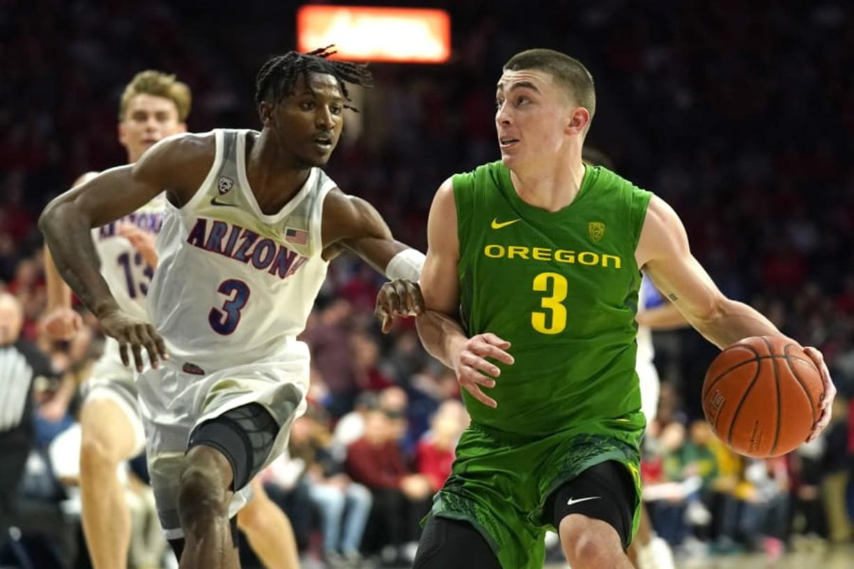 Oregon guard Payton Pritchard, right, drives on Arizona guard Dylan Smith during the first half of an NCAA college basketball game Saturday, Feb. 22, 2020, in Tucson, Ariz.