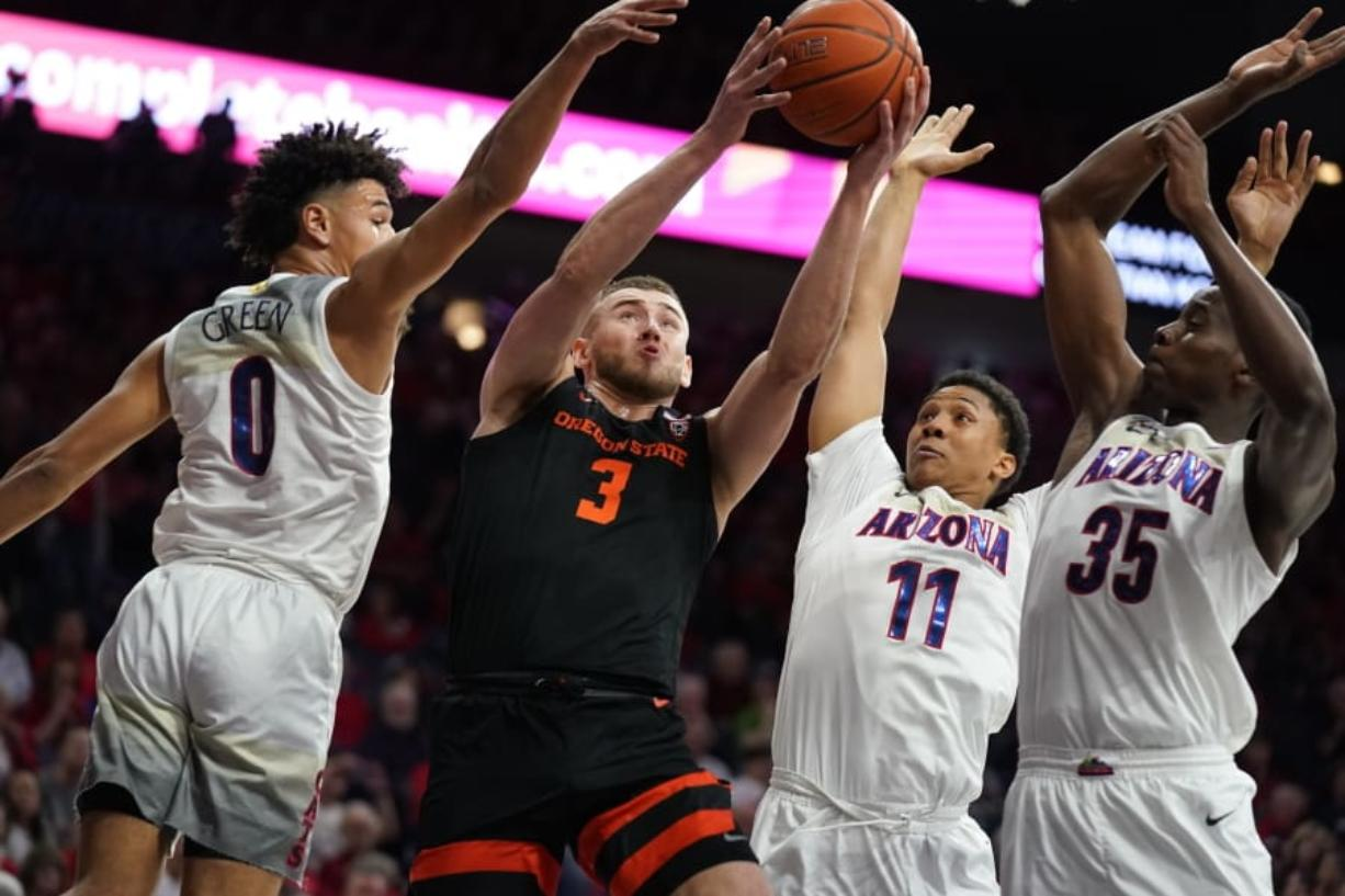 Oregon State forward Tres Tinkle (3) drives between Arizona guard Josh Green (0), Ira Lee (11), and Christian Koloko (35) during the first half of an NCAA college basketball game Thursday, Feb. 20, 2020, in Tucson, Ariz.