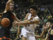 Oregon's Will Richardson, center, passes the ball between Oregon State's Kylor Kelley, left, and Tres Tinkle, right, during the first half of an NCAA college basketball game in Eugene, Ore., Thursday, Feb. 27, 2020.