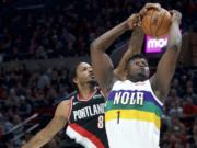 New Orleans Pelicans forward Zion Williamson, right, shoots and scores despite the defense of Portland Trail Blazers forward Trevor Ariza during the first half of an NBA basketball game in Portland, Ore., Friday, Feb. 21, 2020.